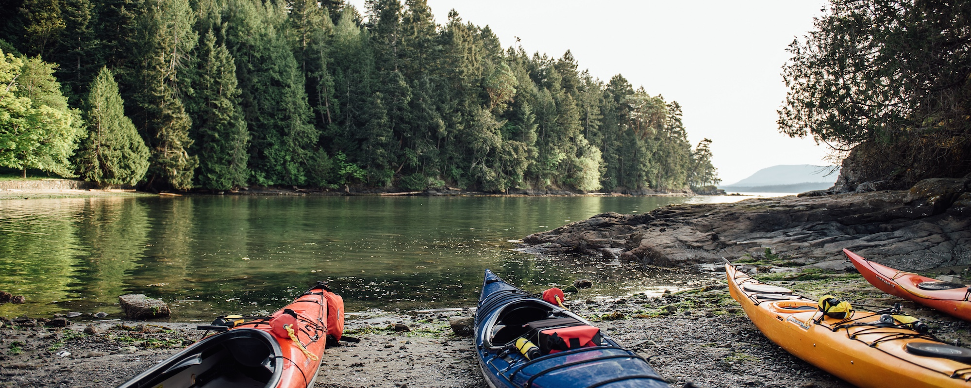 kayas on the southern gulf islands' shore belonging to  Pender Island Kayak Adventures