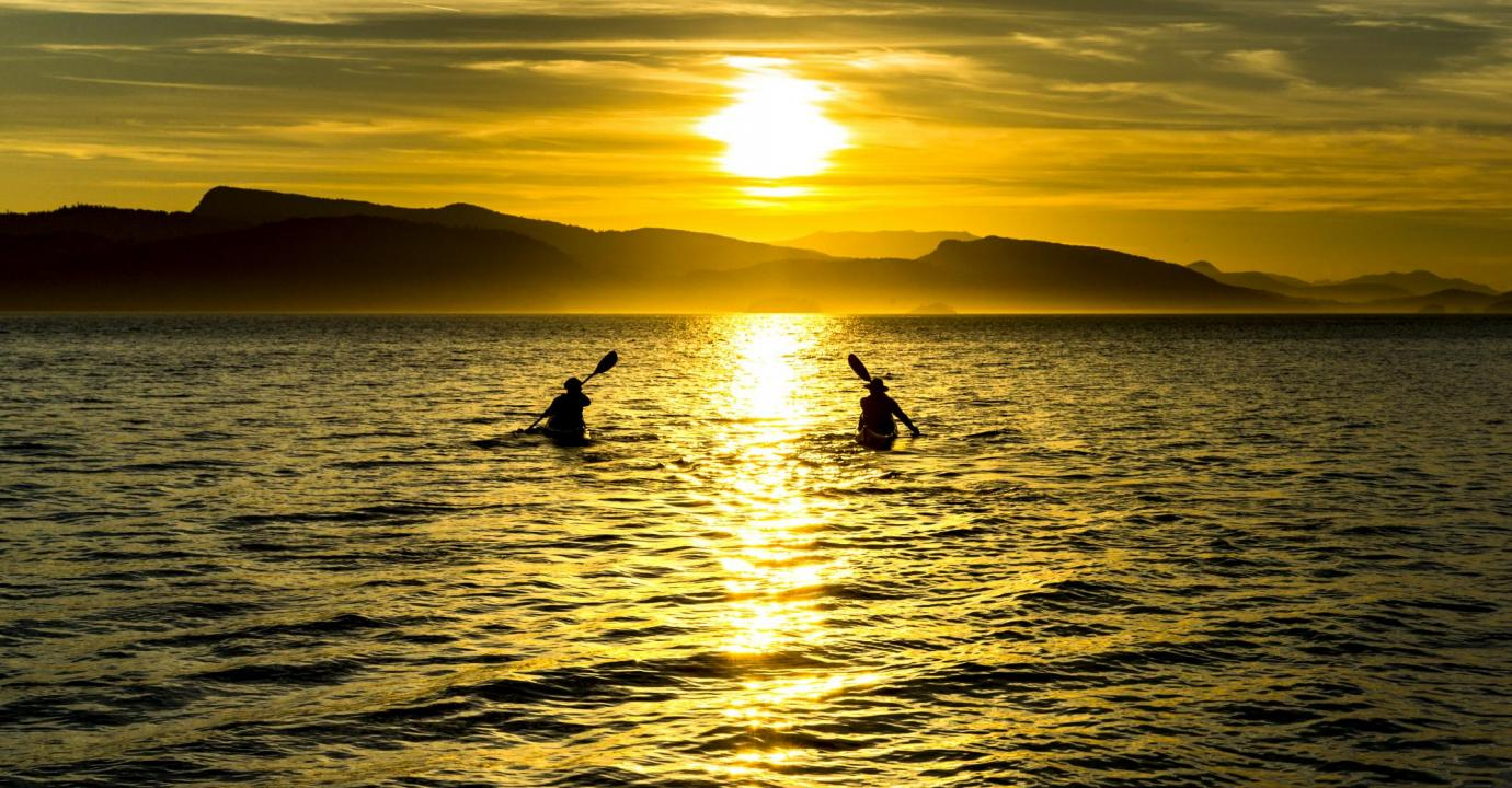 Kayaks paddling into the sunset, Southern Gulf Islands, British Columbia